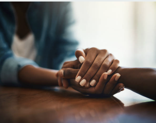 Two black people hold hands because of a loss